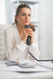 Thoughtful modern business woman holding phone
