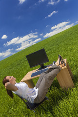 Woman Relaxing at Office Desk in Green Field