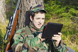 Young recruit with tablet PC and optical rifle in forest
