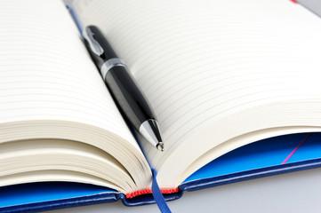 Datebook with black pen close up
