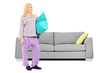 Blond woman in pajamas standing in front of a sofa