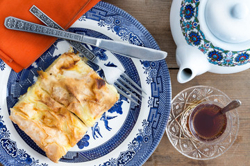 Slice of Turkish borek served with a cup of tea