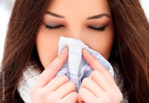 woman with a cold holding a tissue, outdoors