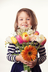 Cute child holding fresh spring flowers