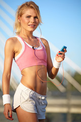 Young fit woman resting and listening to mp3 music outdoors