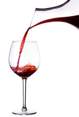Red wine in decanter pouring into wine glass. isolated on white