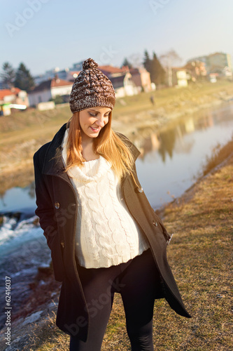 Pretty young pregnant woman taking a walk by the river