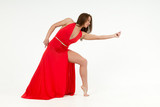 girl in red dress shows element of dance in white studio