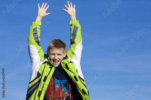 Joyful boy against the blue sky