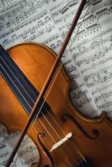 Wertvolle alte Geige mit Bogen liegt auf einem Notenblatt
