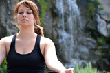 woman practicing yoga with a waterfall background