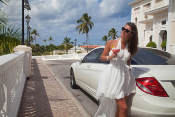 Beautiful brunette young woman in white dress near car.