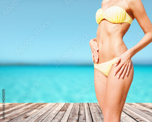 closeup of female body in bikini at beach
