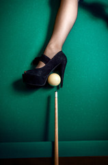 Closeup shot of high heels shoe as billiard pocket
