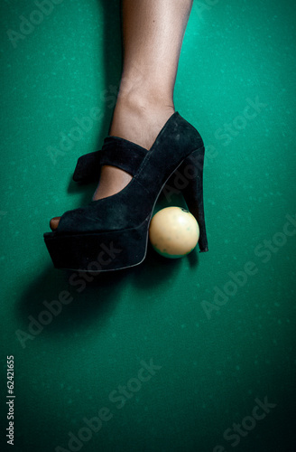 white billiard ball stuck in high heel black shoe