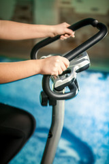 Closeup shot woman riding exercise bike