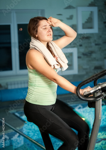 woman training on exercise bike against swimming pool