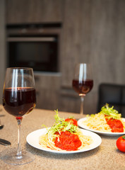Spaghetti with tomato sauce and red wine in a kitchen