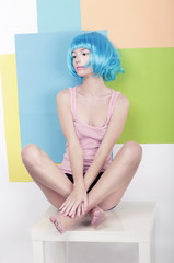 Funky Girl in Azure Wig Sitting in Studio on White Chair
