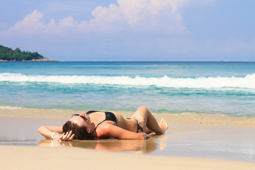 Young woman enjoying summer vacation on tropical white beach