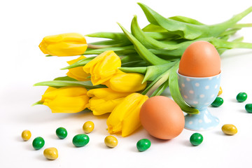 Bouquet of yellow tulips, two eggs and sweets