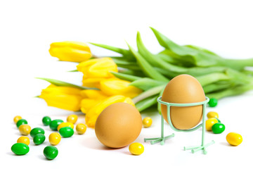 Two eggs against yellow tulips