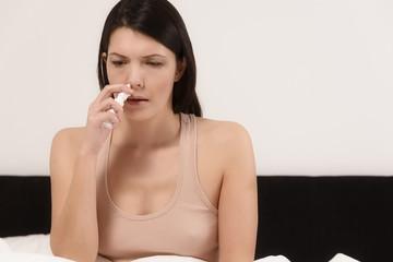 Frau benutzt Nasenspray im Bett