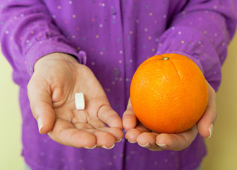 Woman hand with pills medicine tablets and orange