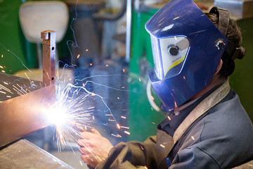 Welder working at factory with sparks and smoke