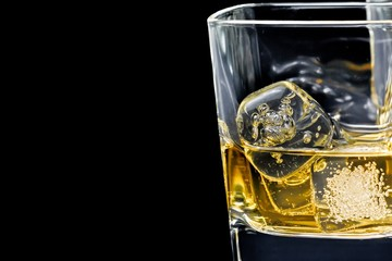 glass of alcoholic drink with ice on black background