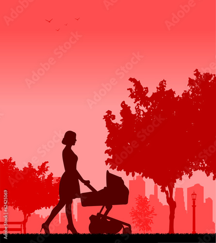 Young mother pushing the stroller and walk through the park