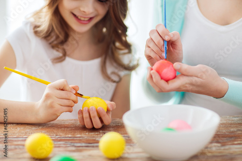 close up of little girl and mother coloring eggs