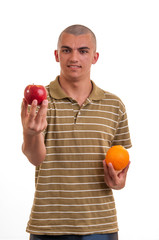 Studio shot of a young man who offers apples instead of orange,