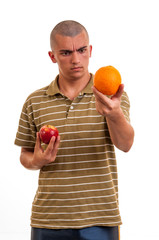 young man comparing orange to red apple