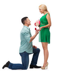 smiling couple with flower bouquet and ring