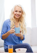 smiling woman with cup of tea having breakfast