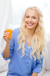 smiling woman with glass of orange juice at home