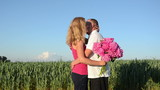 girl kisses guy and hug bouquet of flowers back