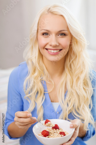 smiling woman with bowl of muesli having breakfast