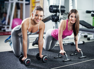 Cute Sporty girls doing exercise in a fitness center.