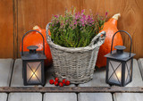 Red heather in wicker basket, pumpkins and lanterns