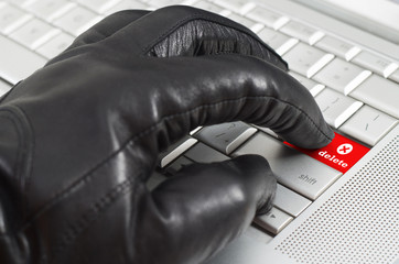 Online delete concept with hand wearing black leather glove pres