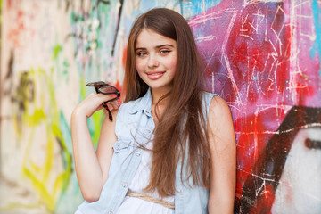 hipster girl outdoors stands near a graffiti wall