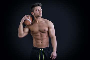 Muscular american football player standing with ball