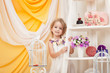 Smiling little girl posing in decorated studio
