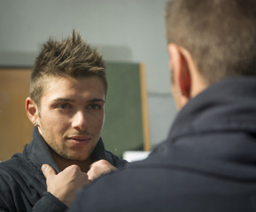 Handsome young man looking at himself in mirror