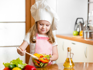 kid making salad at kitchen