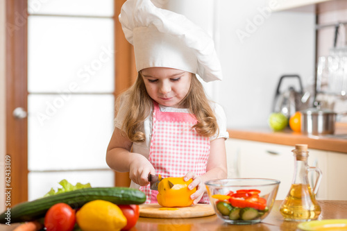 Kid girl weared as cook cutting vegetables