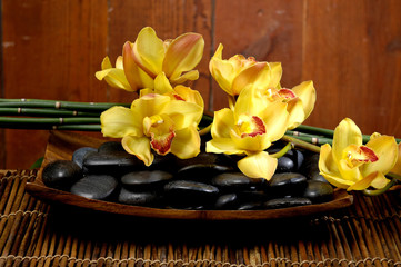 zen stones and branch yellow orchid in the bowl on mat