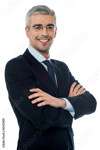 Smiling senior businessman with arms crossed